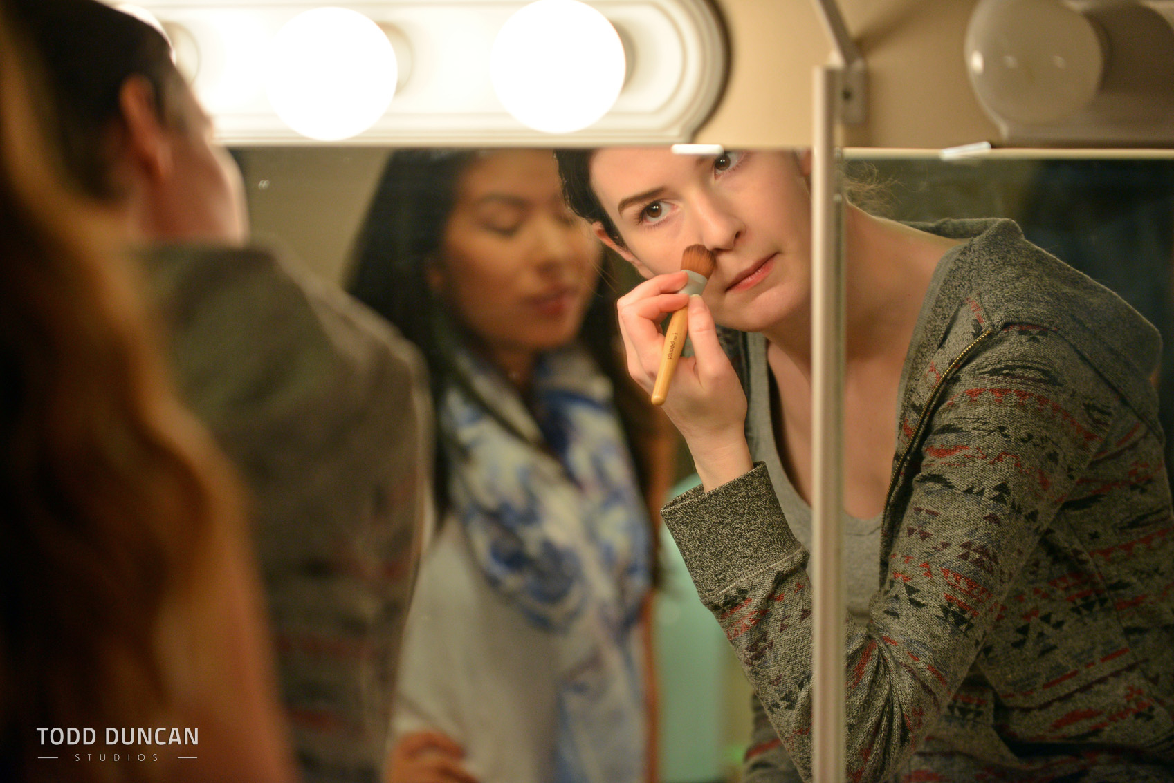 Backstage, applying makeup in the mirror.