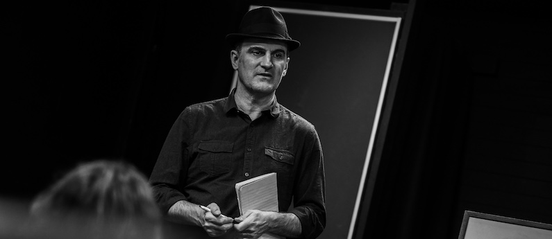 An acting instructor looking dapper in a fedora. The photo is black and white.