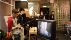 A studio set up, showing behind the scenes with the lighting and sound people working their equipment.