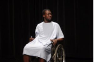 An actor playing a person in a wheelchair; he is wearing a hospital gown.