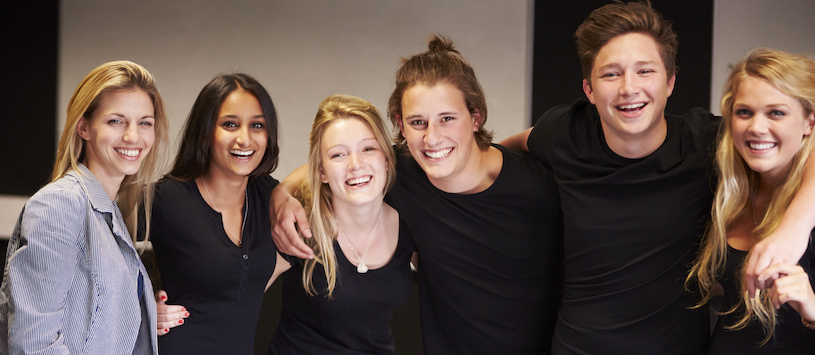 A group of young adult theatre actors, arm in arm, smiling